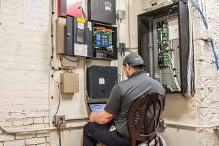 Koorsen Technician Monitoring Fire Alarm Panel for Testing