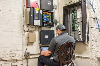 Koorsen Technician Monitoring Fire Alarm Panel for Testing