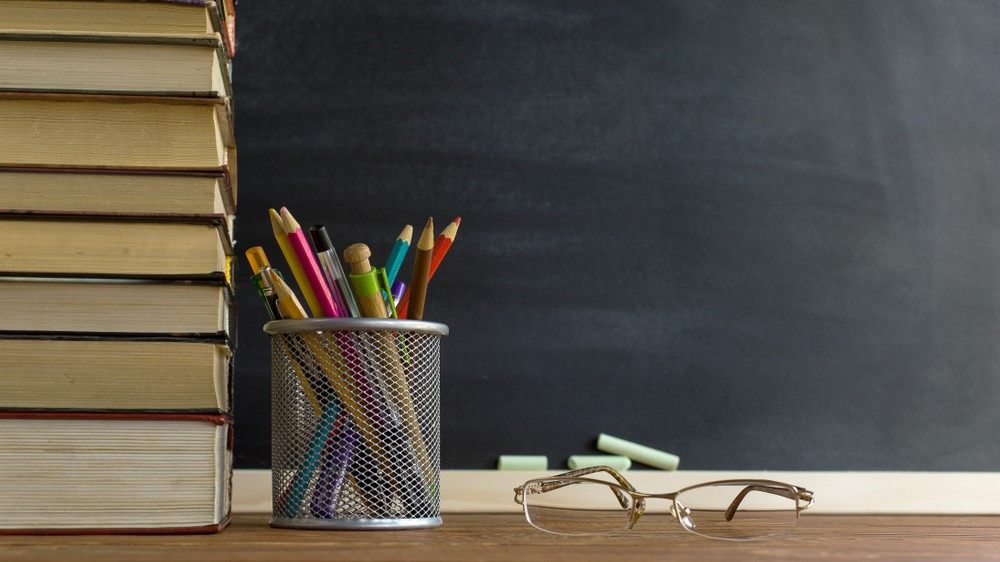 Teacher's desk with books,writing utensils, and glasses on top
